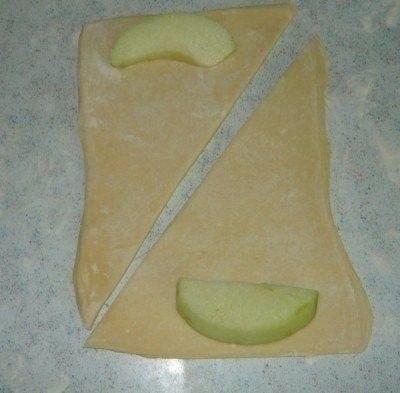 Слойки с яблоками. Ингредиенты:- 1 банка спрайта- 2 упаковки слоеного теста- 2 яблока- 1стакан сахара- 300 г сливочного масла- ванилин- корицаПриготовление:1. Яблоки почистить, нарезать