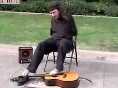 Парень играет ногами на гитаре