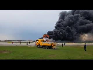 Первые секунды после посадки горящего борта в Шереметьево. Люди, спасшиеся из самолёта, бегут по полосе